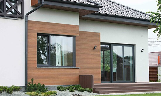 Дом из газобетона с оштукатуренным и отделанным планкеном фасадом